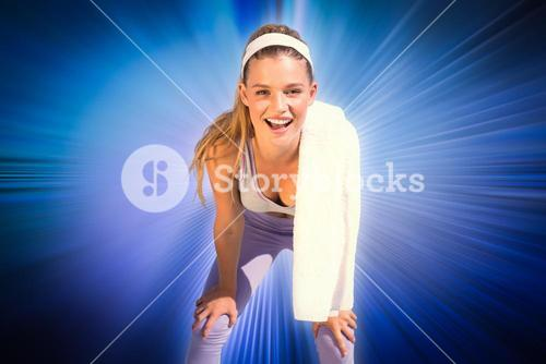 Composite image of sporty smiling blonde standing on the beach with towel