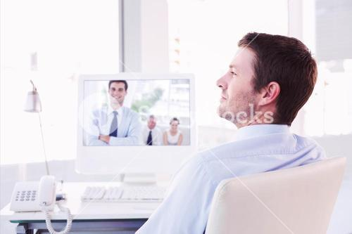Composite image of smiling businessman sitting at his desk