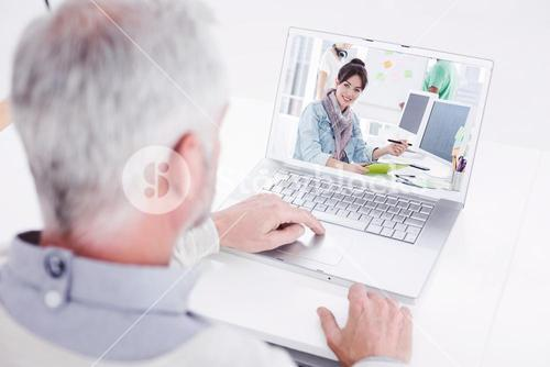Composite image of closeup rear view of a grey haired man using laptop at desk