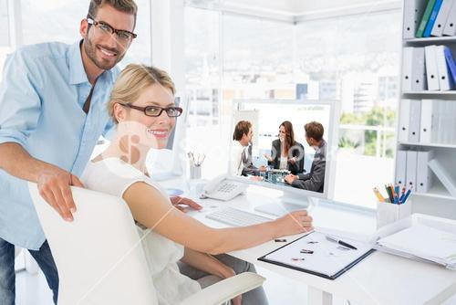 Composite image of attractive businesswoman laughing with her team