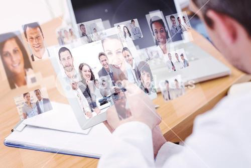Composite image of doctors using laptop and digital tablet in meeting