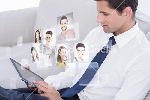 Composite image of attractive businessman using digital tablet