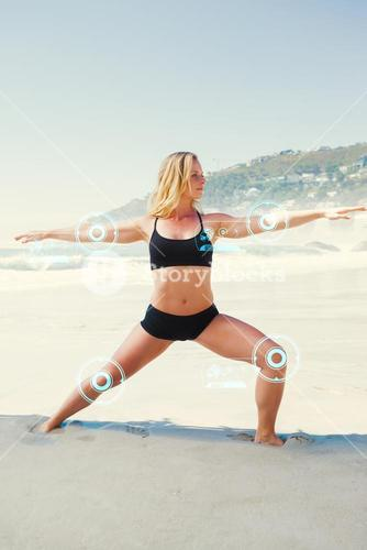 Composite image of fit blonde in warrior pose on the beach