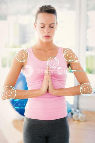 Composite image of woman with joined hands and eyes closed at fitness studio