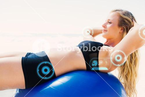 Composite image of fit blonde doing sit ups on exercise ball at the beach