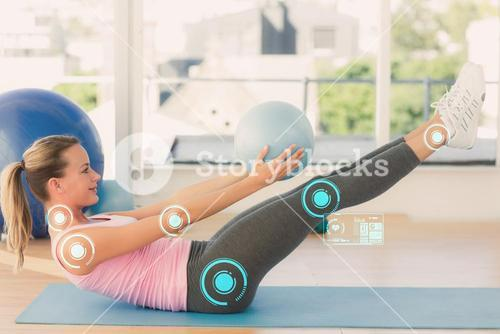 Composite image of sporty young woman stretching body in fitness studio