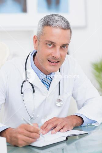 Doctor writing on diary at his desk