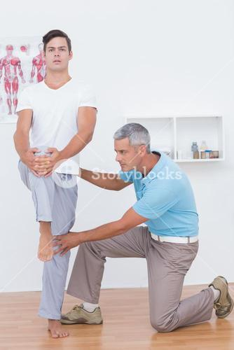 Doctor examining his patient legs