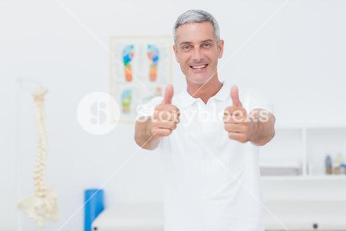 Happy doctor looking at camera with thumbs up