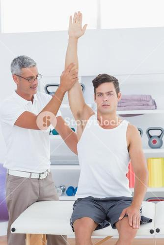 Doctor raising a young man arm