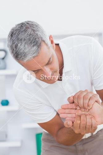 Doctor examining a male patients hand