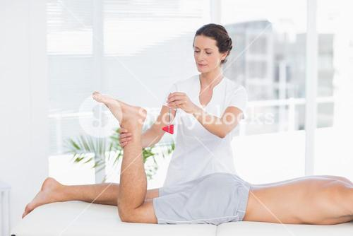 Physiotherapist using reflex hammer