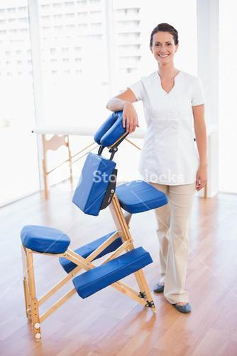 Smiling therapist standing with massage chair