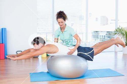 Trainer with man on exercise ball