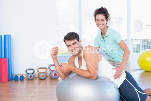 Trainer helping man with exercise ball