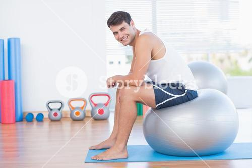 Smiling man sitting on exercise ball and looking at camera