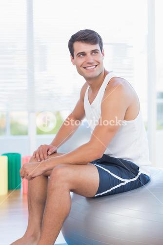 Smiling man sitting on exercise ball
