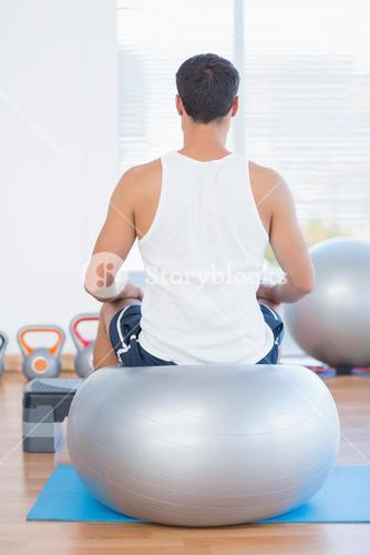 Man sitting on exercise ball