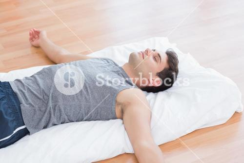 Man relaxing on exercise mat