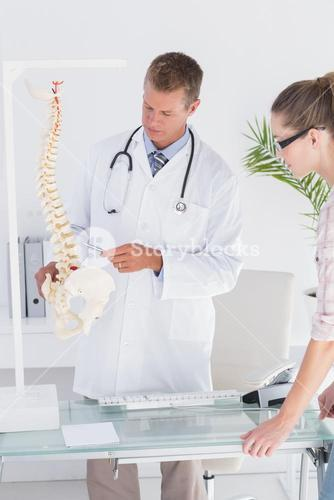 Doctor explaining anatomical spine to his patient