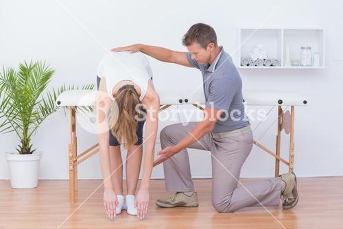 Doctor stretching a woman back