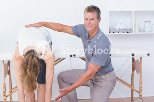 Happy doctor stretching a woman back