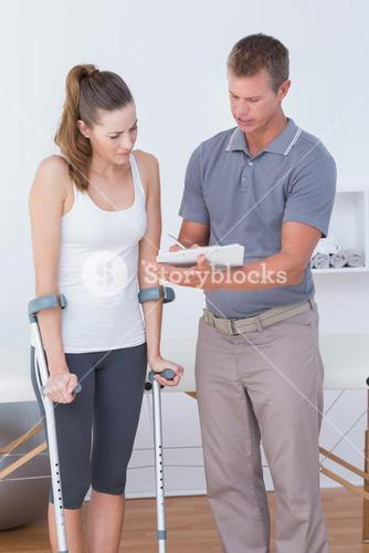 Woman with crutch speaking with his doctor