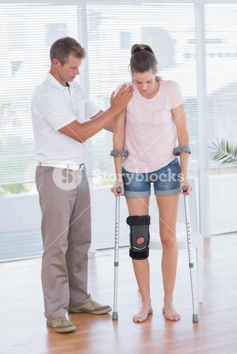 Doctor helping his patient walking with crutch
