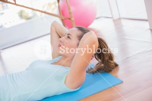 Woman lying on exercise mat