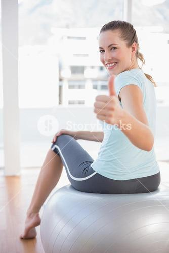 Woman looking at camera and sitting on exercise ball