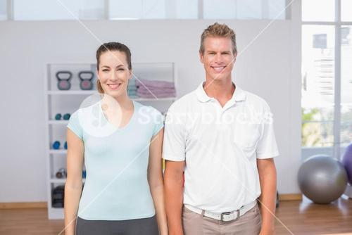 Smiling woman with her trainer looking at camera