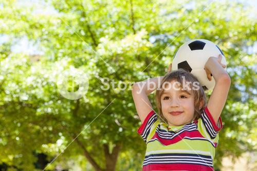 Happy little boy holding football