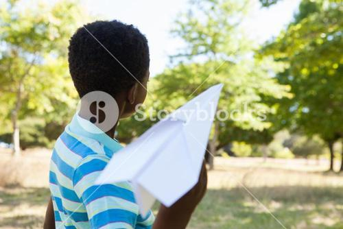 Cute little boy with paper airplane