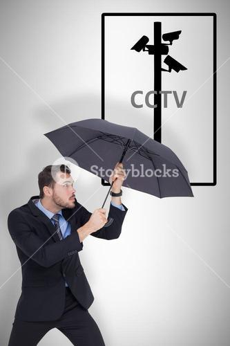 Composite image of businessman holding umbrella to protect himself