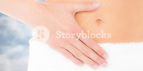 Composite image of mid section of a fit woman with hand on stomach