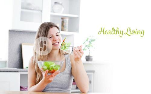 Healthy living against charming woman eating a salad in the kitchen