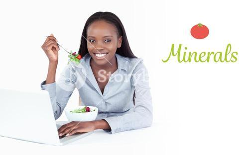 Minerals against joyful businesswoman working with a laptop while eating a salad