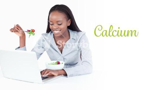 Calcium against young businesswoman working with a notebook while eating a salad