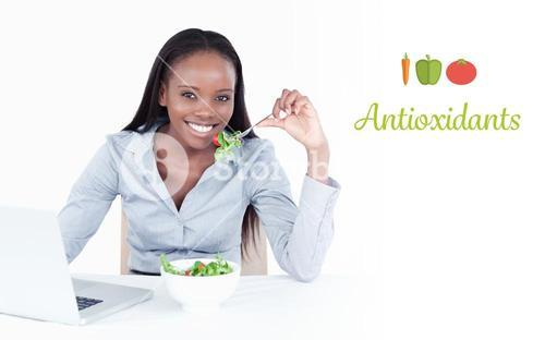 Antioxidants against cute businesswoman working with a notebook while eating a salad