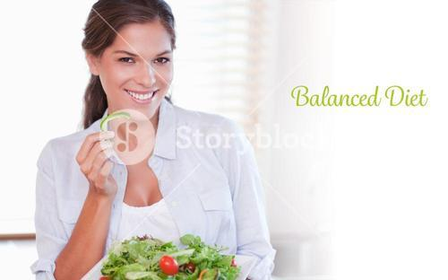 Balanced diet against smiling woman eating a salad