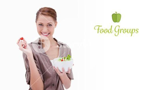 Food groups against woman with bowl of salad and small tomato in her fingers