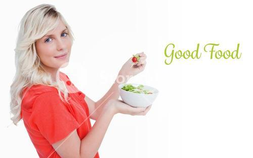 Good food against side view of a young blonde woman eating vegetable salad