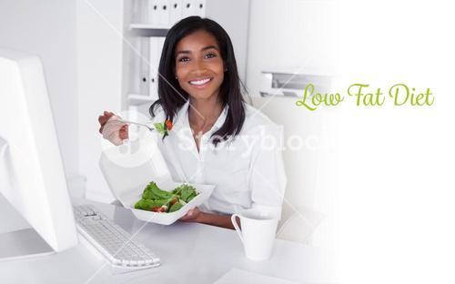 Low fat diet against happy pretty businesswoman eating a salad at her desk
