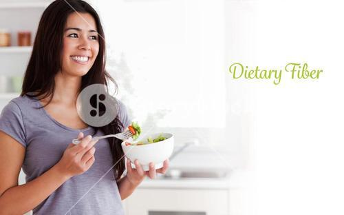 Dietary fiber against attractive woman enjoying a bowl of salad while standing