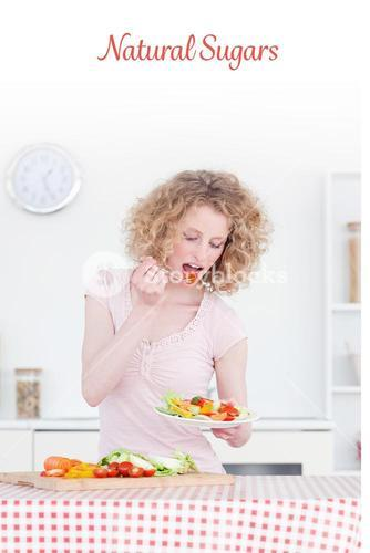 Natural sugars against good looking blonde woman eating some vegetables in the kitchen