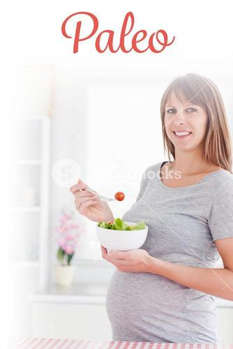 Paleo against charming pregnant woman eating a cherry tomato while standing
