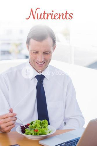 Nutrients against smiling businessman eating a salad on his desk