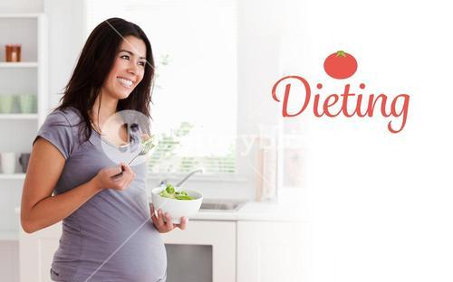 Dieting against beautiful pregnant woman holding a bowl of salad while standing