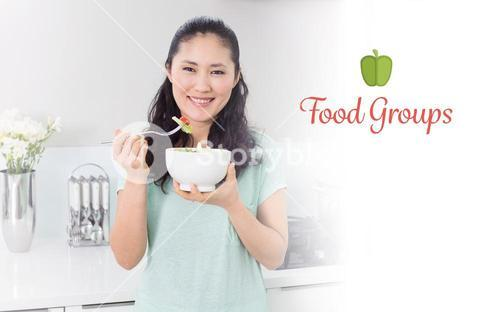 Food groups against smiling young woman with a bowl of salad in kitchen