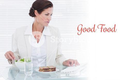 Good food against businesswoman using computer while eating salad at desk